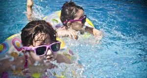 two young kids wearing sunglasses, using float ring in the Gaillimore Community pool