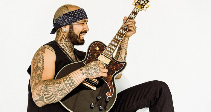 side image of Nahko sitting, playing guitar; Nahko and Medicine For The People