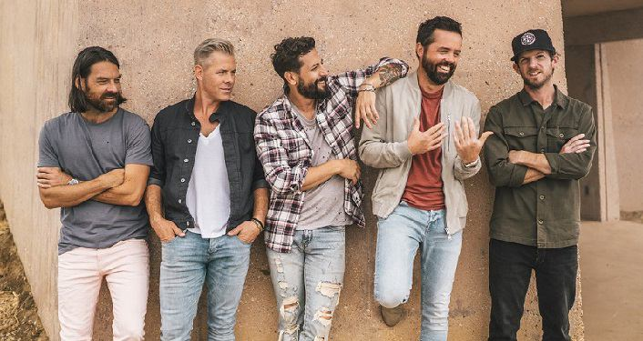 Image of Acclaimed country band Old Dominion standing against a wall, laughing.