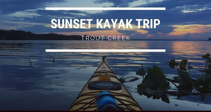 view of kayak looking towards sunset; text: Trout Creek Sunset Kayak Trip