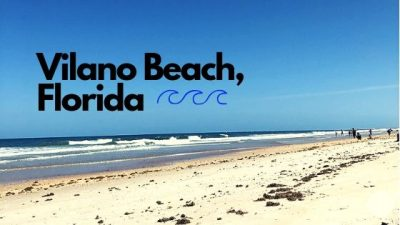 "Image is of the beach, including sand, water, seaweed, and people. Image has text over it reading ""Vilano Beach, Florida""."