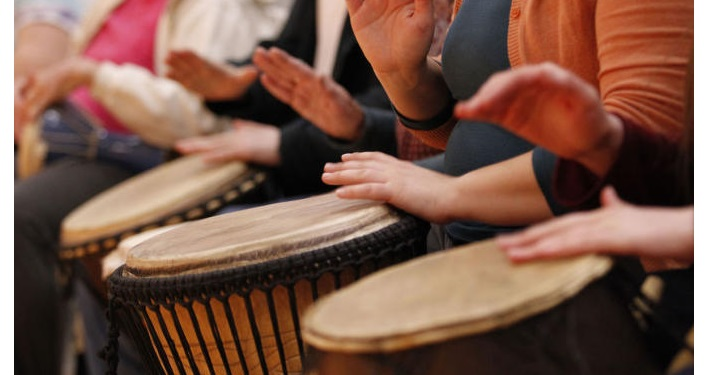 Image of people in a line drumming at a community Drumming Event