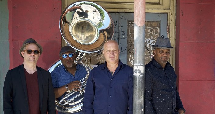 press photo of Mad Skillet taken in New Orleans; 4 men, one holding a tuba