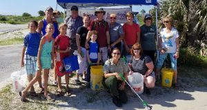 image of park ranger and men and women, three or four young boys and girls holding trash bags, buckets for Coastal Clean-up at Anastasia