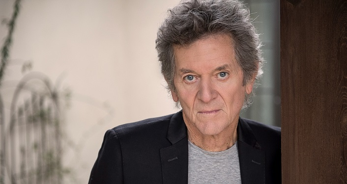 press photo of American roots singer-songwriter Rodney Crowell , wearing light grey shirt, black jacket