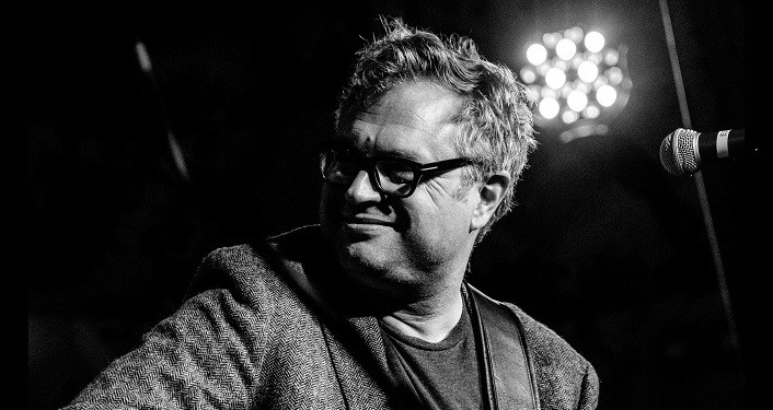 black and white press photo of Steven Page, co-founding member of Barenaked Ladies, holding a guitar- his head turned to his right