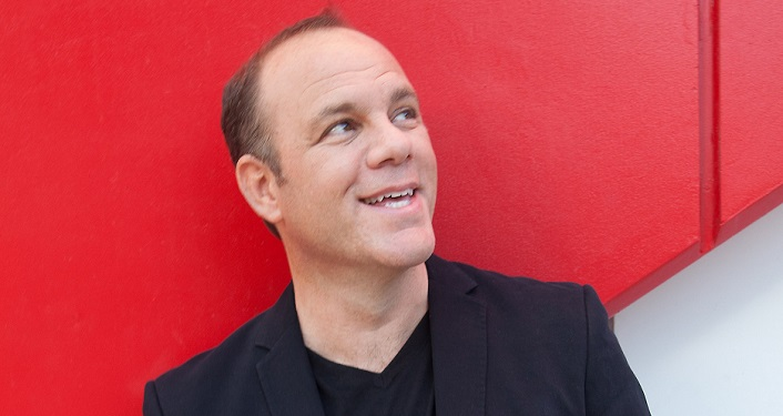 image of Comedian Tom Papa looking towards his left; red background; he's dressed in black t-shirt with black jacket;