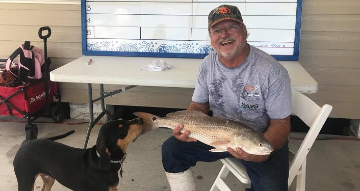 image of man sitting holding a fish cut during Wildwood Inshore Fishing Tournament; brown dog is sniffing at fish