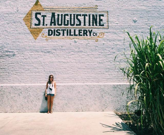 This image contains a woman standing in front of the St. Augustine Distillery.