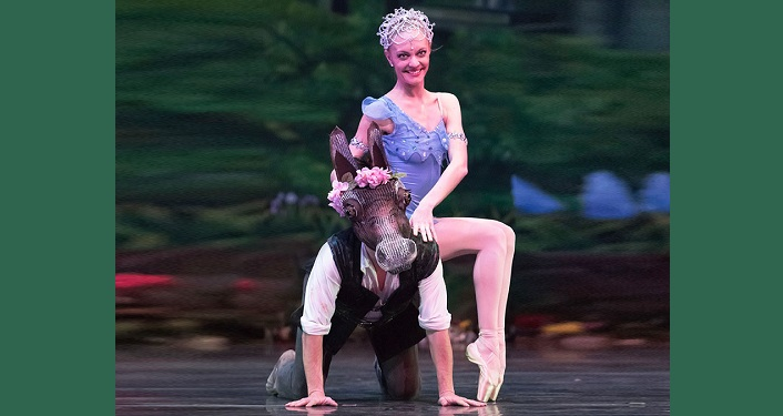 """photo of female ballet dancer dressed in lilac, wearing a crown sitting """"side saddle"""" on back of male on his knees wearing donkey's head mask."""