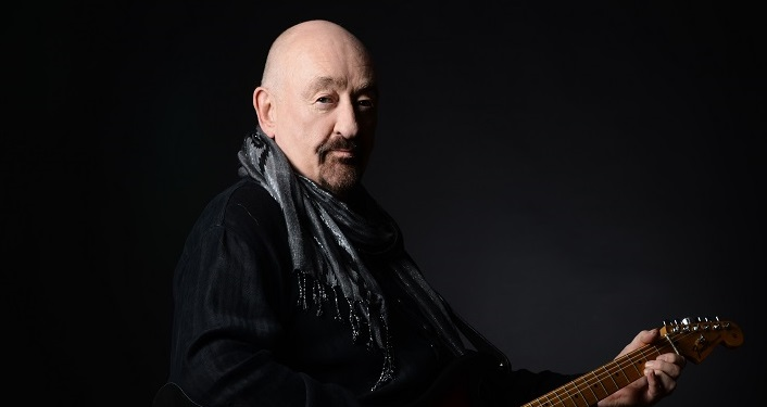 press photo of Dave Mason sitting, holding his guitar looking at camera; bald man with a mustache