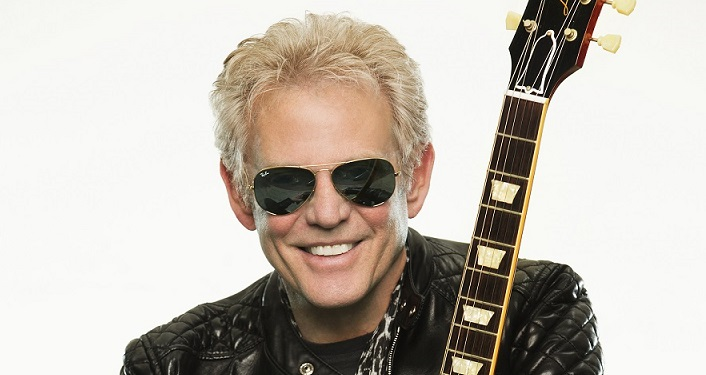 photo of Don Felder, renowned former lead guitarist of The Eagles, from top of shoulders up; holding a guitar, wearing sunglasses.