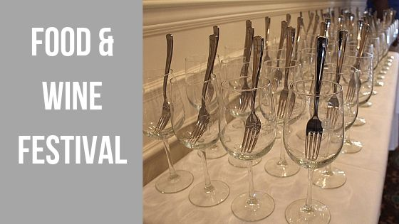 "Image contains wine glasses with forks in them and text that reads ""Food and Wine Festival""."