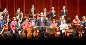 photo of Jacksonville Symphony Orchestra; men and women on stage playing various instruments