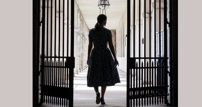 image of wrought-iron gates with silhoutee of woman during Lightner Upstairs - Downstairs Tour