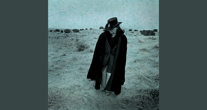 photo of Country music torchbearer Marty Stuart standing in a straw covered field. His clothers are black, he's got on a black hat and his head is bent down, a black cape is around his shoulders. Marty Stuart The Pilgrim