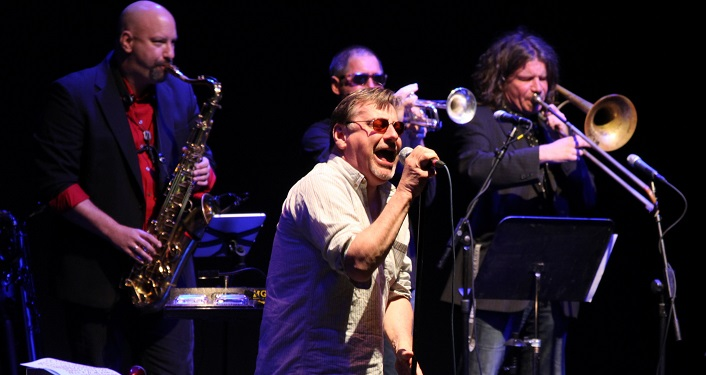 press photo of musicians, Southside Johnny and the Asbury Jukes, performing onstage; one singing, couple playing trumpets, one playing saxaphone