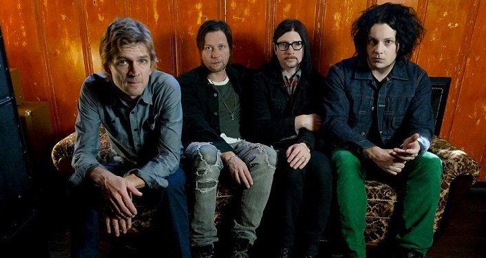 press photo of Chart-topping rock group The Raconteurs; four guys sitting on a couch