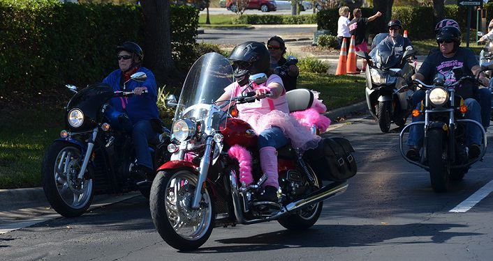 photo of motorcycle riders, one dressed in a pink tutu, participating on Unity Pink Motorcycle Ride