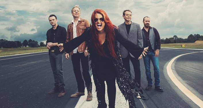 image of Wynonna Judd and her band, The Big Noise, standing on a highway. Wynonna is in front of the band standing with her hers out to her sides and her mouth open wide like she's yelling.