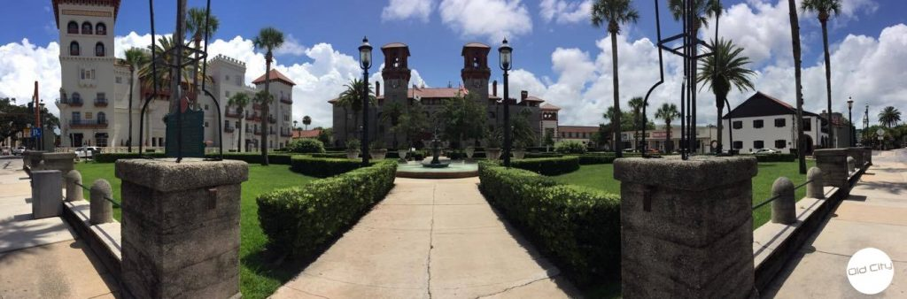 Image contains a large building and lush grounds.