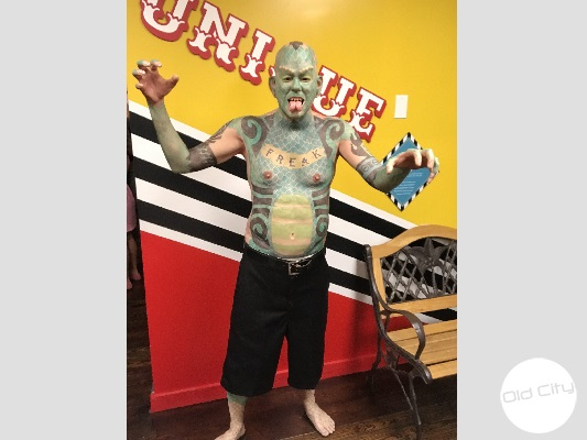 Image contains a life-size replica of the lizard man.