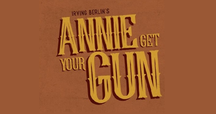 text in gold color, Annie Get Your Gun with brown background