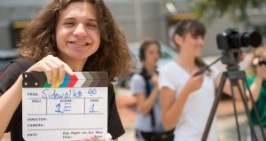 photo of young man holding clapper board with two young woman in background, one filming with a camera on tripod for International Student Film Festival