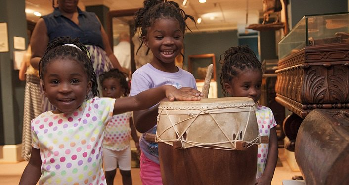"image of three little girls around a drum, two beating on the drum during ""Year of Music"" Museum Day Celebration at Lightner"