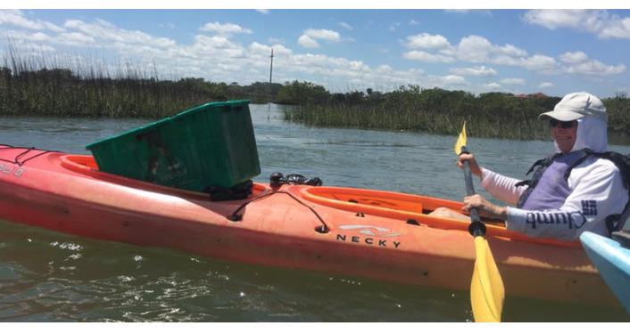 image of kayaker carrying waste receptacleduring Helen Mellon Schmidt Waterway Cleanup
