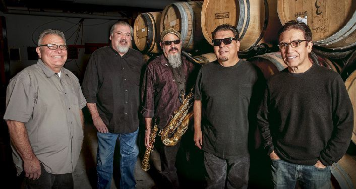 image of Grammy award-winning rockers Los Lobos, 5 middle-age guys standing in front of wine casks, middle one with saxaphone around his neck