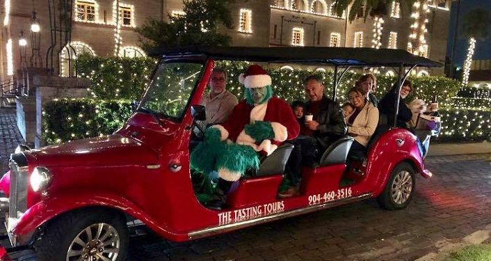 iamge of person dressed as Grinch driving a roadster during Lights, Carriage & Holiday 'Cheer' Tours
