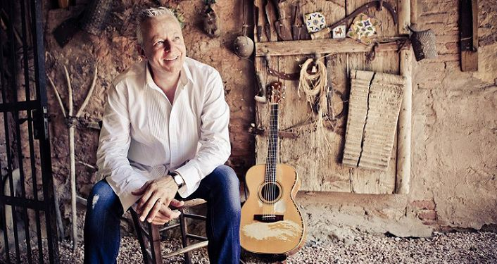 photo of Tommy Emmanuel sitting on stool his guitar propped against the wall. he's wearing jeans and a white long-sleeved shirt.