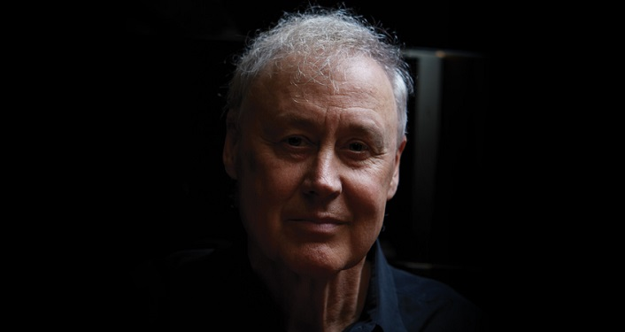 press photo of Bruce Hornsby; head shot with black background. Man with greyish hair