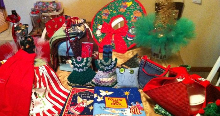 image of handmade Christmas items on a table; crocheted wreath and socks, books, ..for the Christmas Market at Shores United Methodist Church