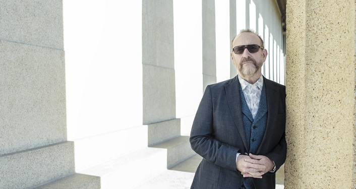 Image of middle-aged man with receding hairline, drooping mustache, wearing sports jacket, light blue shirt leaning against pillar; fingers linked together. Colin Hay Press Photo