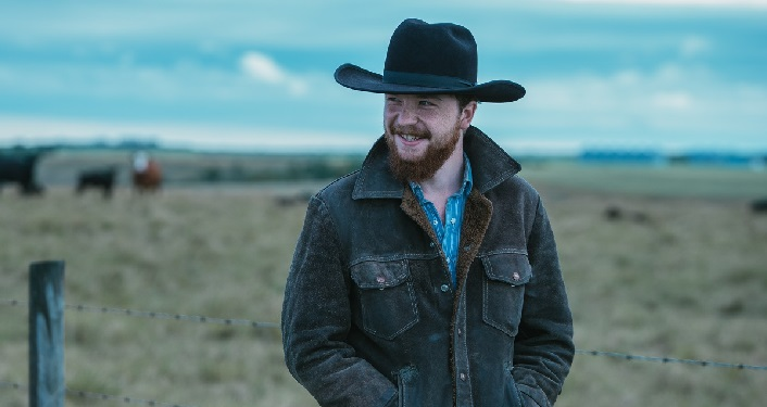 press photo of Rising Americana songwriter Colter Wall; young man with a beard wearing a cowboy hat and heavy jacket standing in a field with cattle behind him