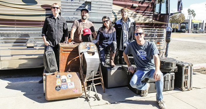 press photo of Donna the Buffalo; five musicians with various instruments standing in front of old bus