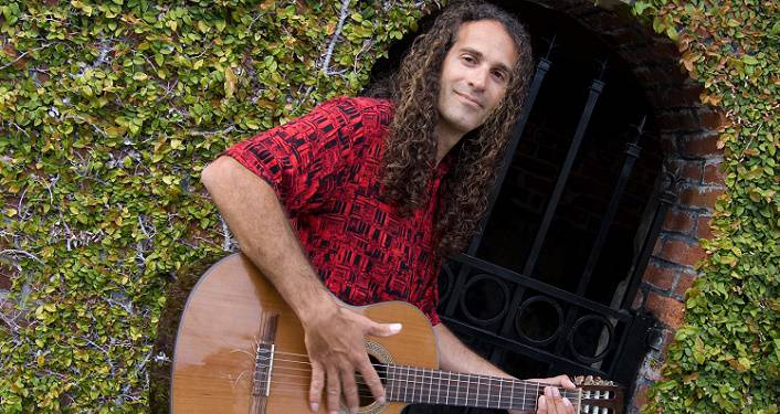 press photo of Fermin Spanish Guitar; long-haired, middle-aged man wearing short-sleeved red print shirt, standing strumming a guitar