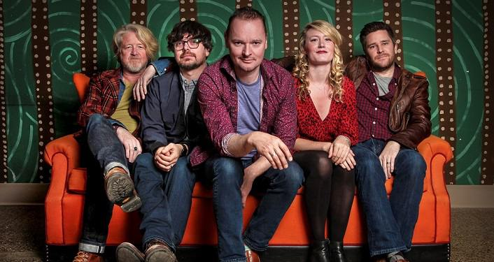 press photo of Irish band Gaelic Storm ; four men and one woman all ages approximately in 30s-40s. All sitting on a couch