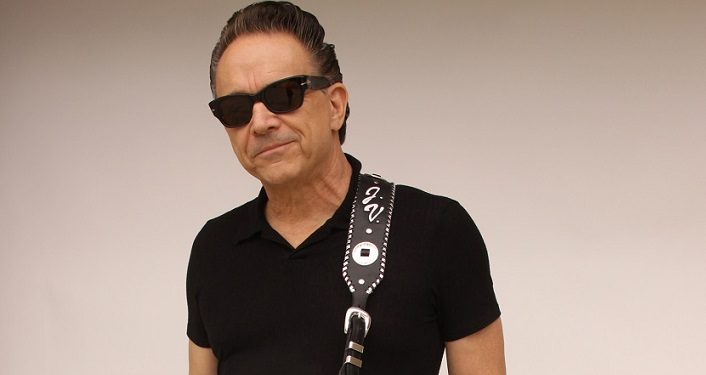 press photo Jimmie Vaughan; middle aged man with dark hair, wearing sunglasses, black shirt with guitar-strap over left shoulder