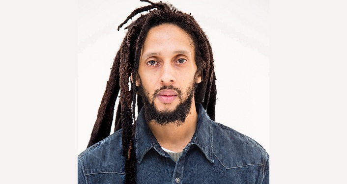 press photo of Roots-reggae musician Julian Marley; middle-aged man with dark hair braided rasta-style, mustache and beard wearing blue collared shirt