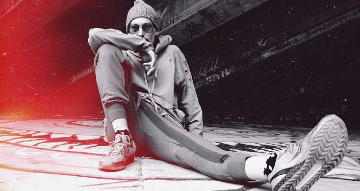 press photo of Roots reggae artist Matisyahu; man sitting on ground dressed in grey sweats, wearing grey cap and sunglasses, right arm propped on right knee that is pulled up.