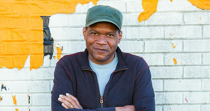 press photo of rootsy, rocking-blues Hall of Famer Robert Cray; black man standing with arms crossed in front of white brick wall with splotches of yellow.