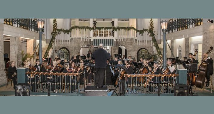 image of the St Augustine Orchestra performing their Holiday Concert at Cafe Alcazar; men & woman dressed in black performing various instruments