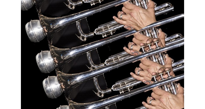 side image of four trumpets being played