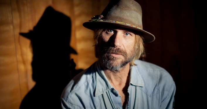 press photo of Alt-country singer/songwriter Todd Snider; middle-aged man with sandy colored hair and mustache wearing light blue collared shirt and a brown fedora