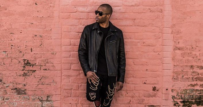 press photo of Celebrated New Orleans funk master Trombone Shorty; black man dressed in black pants, black shirt and jacket wearing sunglasses leaning against a pink wall; his head turned to his right side, right foot pressed against wall