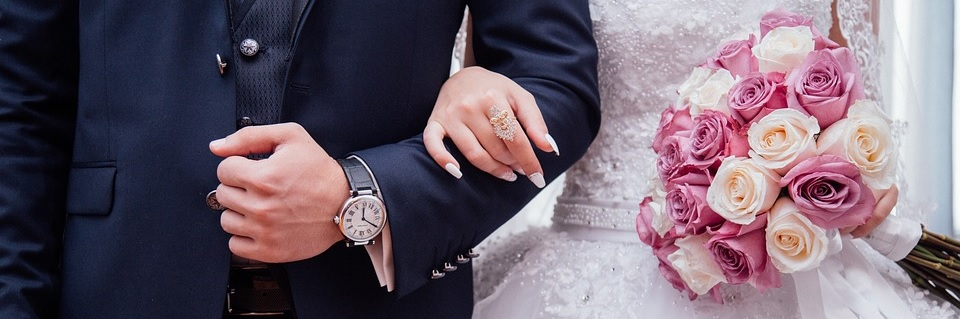 Image contains a close up of a bride and groom locking arms, with flowers in brides hand.