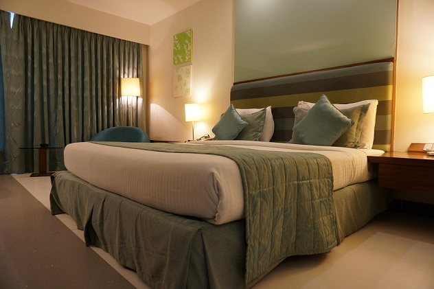 Image contains a dimly lit hotell room with a bed, curtains, and end tables.